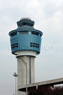An air traffic control tower at an airport on a stormy looking day.