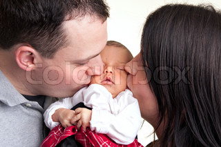 A newborn baby is held by her mother and father as they kiss her cheeks.