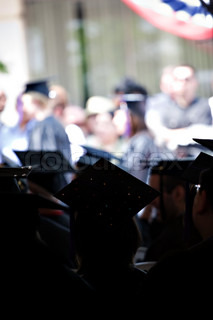 Silhouettes of college or high school graduates wearing the traditional cap and gown.  Shallow depth of field.