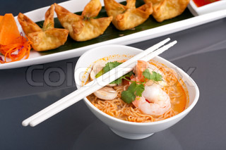 Shrimp and Thai noodle soup bowl with chopsticks along with fried wonton or rangoon type appetizers.
