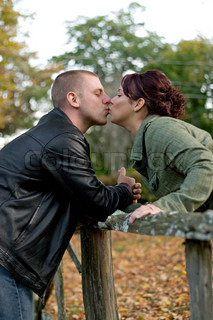 A young happy couple passionately kissing each other outdoors in the fall.