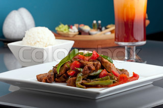 A fresh dish of Thai style roast chile basil duck with mixed vegetables white jasmine sticky rice and thai iced tea.