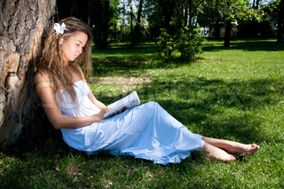 Portrait of the young girl reading in park reading under a tree