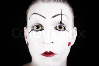 mime face with a theatrical makeup on black background