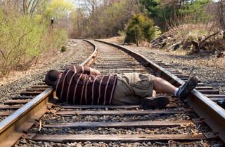 A man laying on the railroad tracks.  Not exactly the smartest thing to do.
