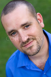 A portrait of a smiling young man with a goatee.
