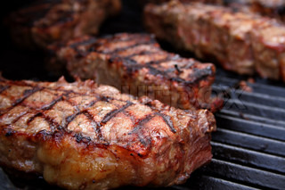 Thick, juicy steaks on a barbecue grill.