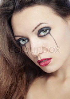 Sad woman with odd makeup. Close-up portrait with natural colors