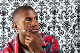 A young African American man in his twenties and his hand on his chin thinking deeply about something in front of a damask style background. Shallow depth of field.