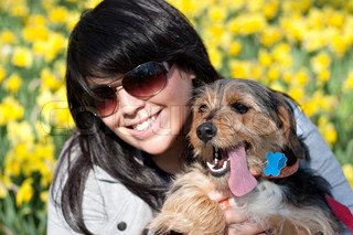 A cute terrier mix breed pup in the arms of a beautiful Spanish woman posing in front of the yellow daffodil flowers in the Spring time. Shallow depth of field.