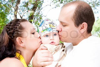two parent kissing their baby boy, summer in park