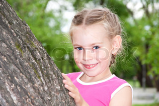 portrait young girl peeping out tree, in summer park