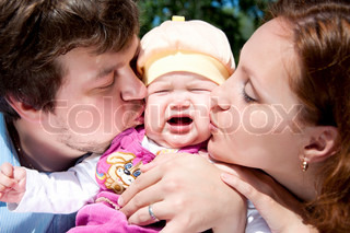 Father and mother kissing a child, the child is crying and sad