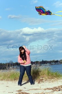 A young woman flying a kite at the sea shore on a nice day.