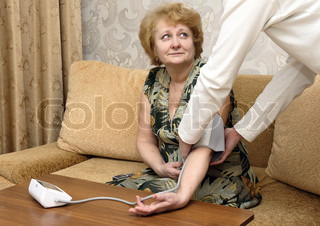 Old woman measures arterial pressure , with doctor helps.