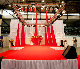 Wedding podium covered with red carpet, studio lights
