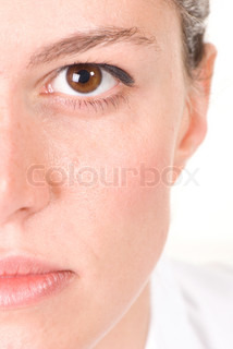 Exactly half of the face of a beautiful young woman with brown eyes on white background