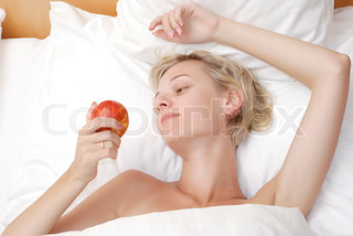 Beautiful young woman eating fruits in bed