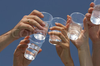 Glasses of water in hands against a blue sky