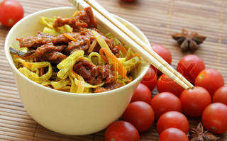 Chinese noodles and fried beef within bowl close-up