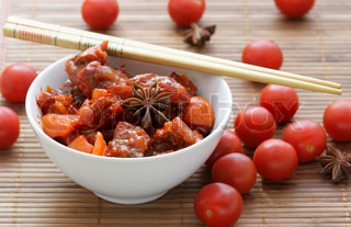 Chinese dish - beef with vegetables and cherry tomatoes close-up