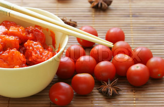 Chinese dish - pork in sour-sweet sauce  and cherry tomatoes close-up