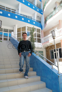 Young man standing on the stairs of modern building