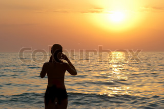 Girl silhouette and sunset on the sea