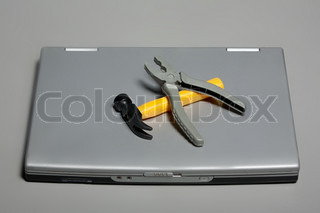A broken laptop with a hammer and pliers. Closeup
