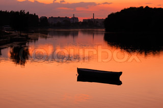 View anchored boat in the reservoir after sunset in quiet summer weather. Khmelnitsky,