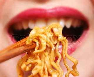 Young chinese woman eating noodles for dinner