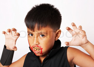 Boy With Fake Teeth And Blood Around His Mouth Dressed For Halloween