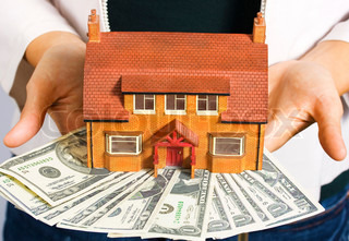 A person holding a miniature house and some dollar bills for making payments