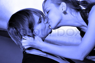 Young attractive couple kissing Image toned in blue color