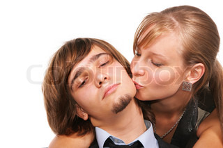 Young girl kissing young handsome guy isolated over white background