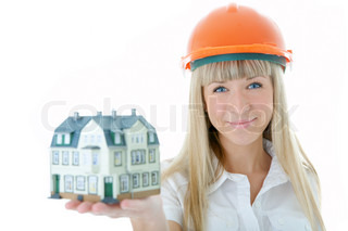 architect woman in helmet with little house on hand over white background