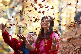 Young couple enjoying the falling leaves in the autumn park