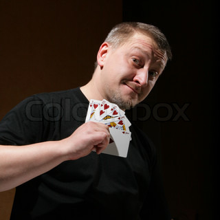 Portrait of the man with royal flush over dark background