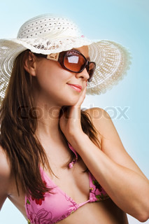 Young beautiful sexy tanned brunette woman in hat and bikini on blue