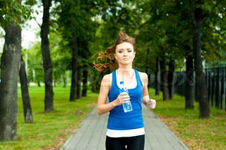 young woman jogging in the park in summer, trees and grass background