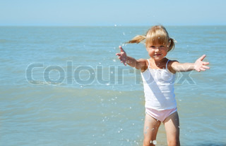 little girl child on the sea under blue sky