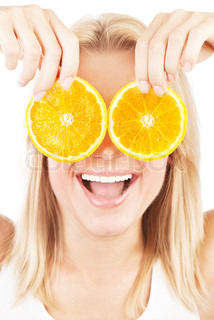 Funny girl portrait, holding oranges over eyes, conceptual image of healthy eating, dieting & skincare