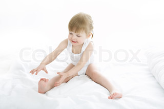 baby doing gymnastics on white background