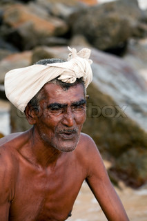 Portrait: the old man from sri lanka sits on the shore of the ocean