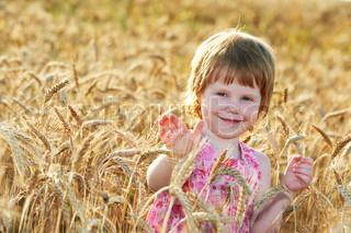 happy little girl child in wheat cereal field in summer