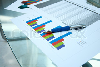 Business documents lay on a glass table at office