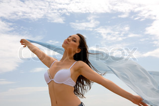 Beautiful girl with eyes closed in a white bras with a flowing chiffon fabric in the wind against the sky
