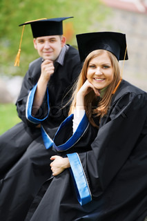 two happy graduate students guy and girl outdoors