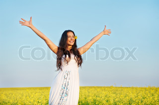 Happy smiling young woman with hands up over yellow green rape meadow