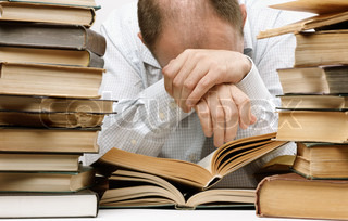 tired man with a lot of books, selective focus on part of head